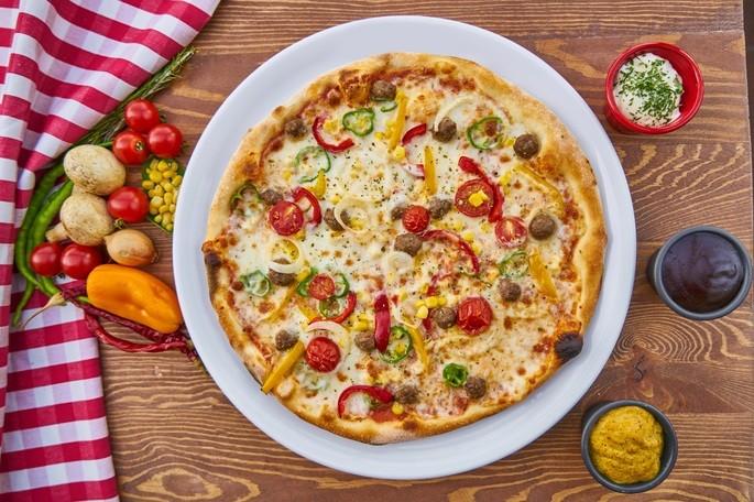 Пицца на белой тарелке, стоящей на деревянном столе, окружённая соусами и овощами с бело-красной скатертью в стороне