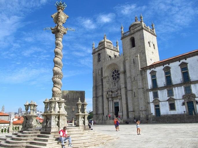 Кафедральный собор Се в Порту на фоне голубого неба, вход в центральный неф собора и позорный столб перед входом