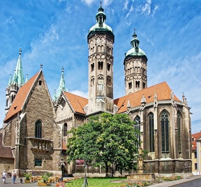 Наумбургский собор в Германии, перед которым растёт дерево, стоят столики уличного кафе и прогуливаются люди