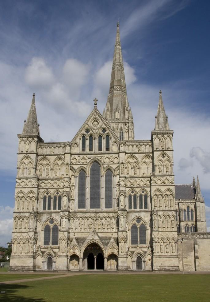 Солсберийский собор в Англии с зелёной лужайкой на фоне голубого неба